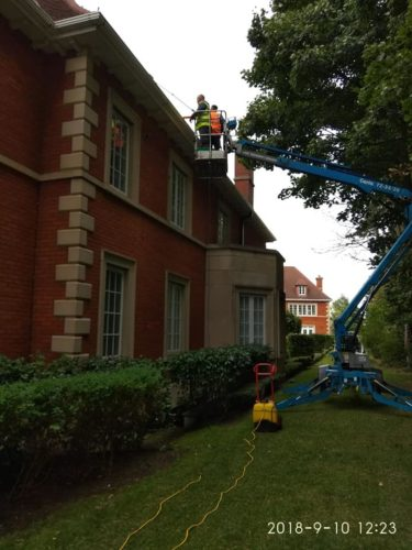 Using a cherry picker to clean difficult windows on a home