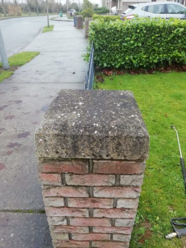 A gatepost covered in moss and black algae which hasn't been cleaned yet - Room With a View Wall Cleaning Meath
