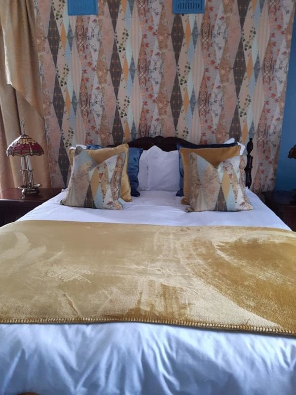 Double bed with gold and coloured blankets B&B