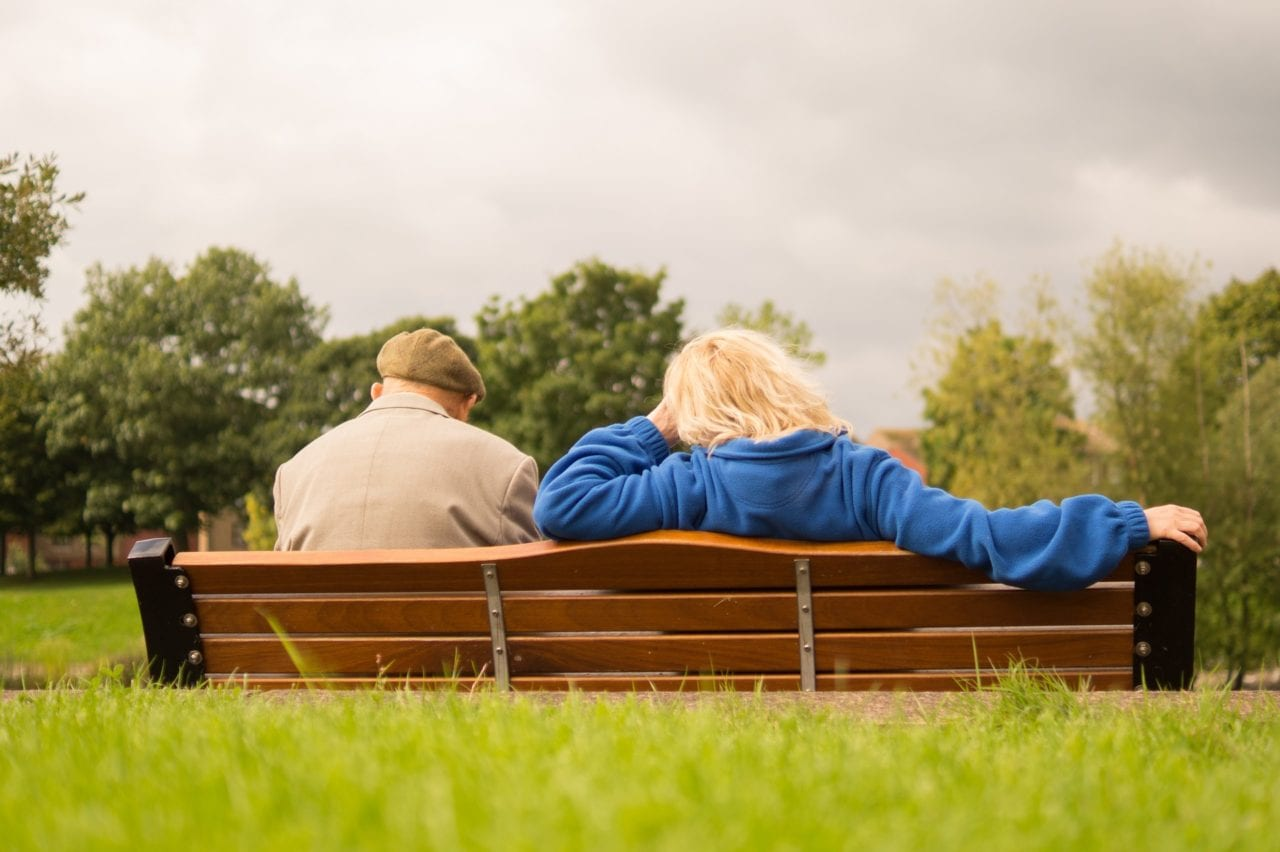 elderly couple sitting on bench protecting and planning future tailored