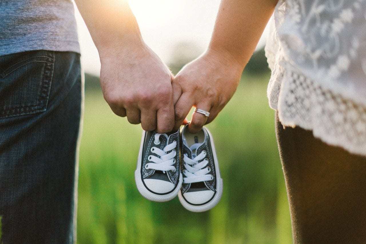 couple holding baby shoes family protection