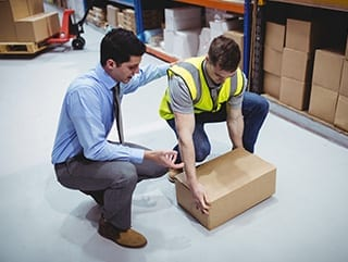 Safety Trainer teaching student how to lift box for manual handling course